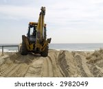 A bulldozer repairs the sand on a New Jersey beach before the busy Summer season. - stock photo