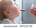 mother feeds baby boy with a... | Shutterstock . vector #299131739