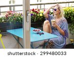 Blond Woman Sitting On Balcony...
