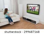 girl sitting on sofa watching... | Shutterstock . vector #299687168