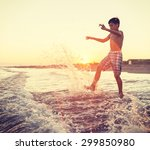 fun kids playing splash at beach | Shutterstock . vector #299850980