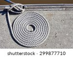 Yacht mooring rope arranged in a very neat spiral on wharf - stock photo