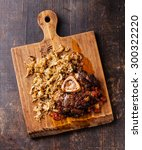 Small photo of Osso buco Veal shank with tomatoes and stewed cabbage on wooden cutting board on wooden background