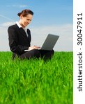 beautiful businesswoman with laptop sitting at the green grass - stock photo