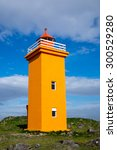 An Orange Lighthouse Seen At...