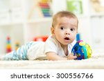 baby boy playing on a carpet at ... | Shutterstock . vector #300556766