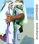 Small photo of poor hawker of cloths and towels on the beach in summer