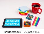 Small photo of Business Term / Business Phrase on Tablet PC - Colorful Rainbow Colors, Cup, Notepad, Pens, Paper Clips, White surface - White Word(s) on a cyan background - Accounts Receivable