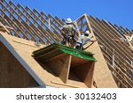 Condo construction with workers on the roof frame - stock photo