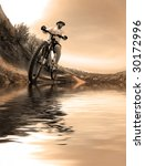 Mountain biking up a trail in the mountains with reflection in water - stock photo
