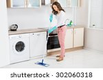 Happy Woman Cleaning Floor Wit...