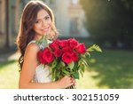 Stock photo smiling girl with bouquet of red roses 302151059
