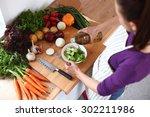 Young Woman Mixing Fresh Salad...