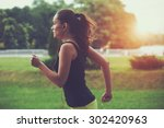 pretty sporty woman jogging at... | Shutterstock . vector #302420963