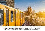 Stock photo panoramic view of berliner u bahn with oberbaum bridge in the background in golden evening light at 303296594