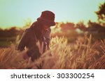 Stock photo woman in meadow travel and sunset in vintage style 303300254
