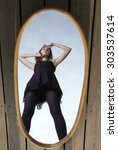 Small photo of thoughtful young woman in black with her reflection in mirror - solitude lonely concept