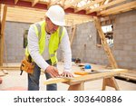 Carpenter Cutting House Roof Supports On Building Site - stock photo