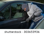 Robber breaking into a car at the parking lot. - stock photo