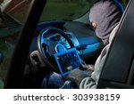 Car thief stealing a car. Hacking into the car system. - stock photo