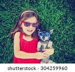 Stock photo a cute toddler girl with red sunglasses on holding a chihuahua with goggles on in the grass in a 304259960