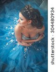 Small photo of Beautiful young woman in gorgeous blue long dress like Cinderella with perfect make-up and hair style