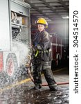 Small photo of Portrait of confident young firewoman spraying water during practice at fire station