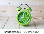 Green Alarm Clock On Wood...