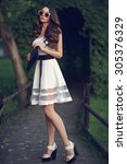 Stock photo young beautiful pretty stylish girl standing and posing at path in park woman in white dress with 305376329