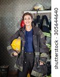 Small photo of Portrait of happy young firewoman holding helmet while standing at fire station