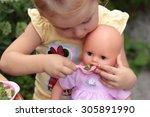 A Little Girl  Feeding Her Doll