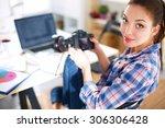 female photographer sitting on... | Shutterstock . vector #306306428