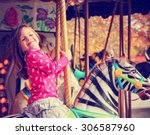 a young girl riding on a merry ... | Shutterstock . vector #306587960