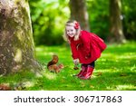 Girl Feeding Squirrel In Autumn ...