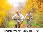 Small photo of Active seniors riding bikes in autumn nature. They having romantic time outdoor.