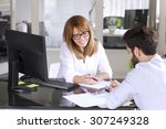 Small photo of Portrait of mature insurance agent giving advise her new client while sitting at office in front of computer. Businesswoman making financial plan.
