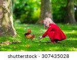 Girl Feeding Squirrel In Autum...