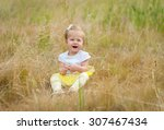 Happy Child Sitting On The Lawn