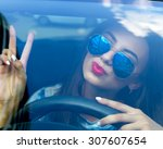 young woman driving her car... | Shutterstock . vector #307607654