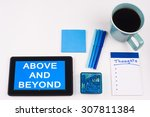 Small photo of Business Term / Business Phrase on Tablet PC - Blues, cup of coffee, Pens, paper clips Calculator with a blue note pad on White - White Word(s) on blue - Above And Beyond