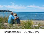Adult man & woman sitting close to each other & hugging while looking out to the ocean, in Parksville, British Columbia, Canada
