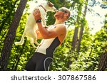 Stock photo smiling happy man in sportswear on nature holding his small dog 307867586