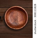 Small photo of Top view of wooden bowl on wooden background