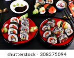 sushi rolls set for japanese style party on black table - stock photo