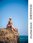 women athlete on a rock by the... | Shutterstock . vector #308554430
