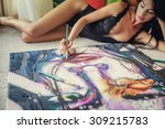 Sexy woman lying on the floor and painting big pattern.