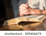 man praying hands on a bible in ... | Shutterstock . vector #309606674