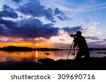 silhouette of photographer taking photo at sunset beside the river - stock photo