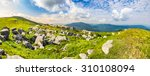 mountain panorama landscape. valley with stones in grass on top of the hillside of mountain range in morning light - stock photo