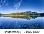 Colorful trees lined the shores of Patricia Lake at Jasper National Park with Pyramid Mountain in the background. The calm lake reflects a mirror image of the mountains and trees. - stock photo